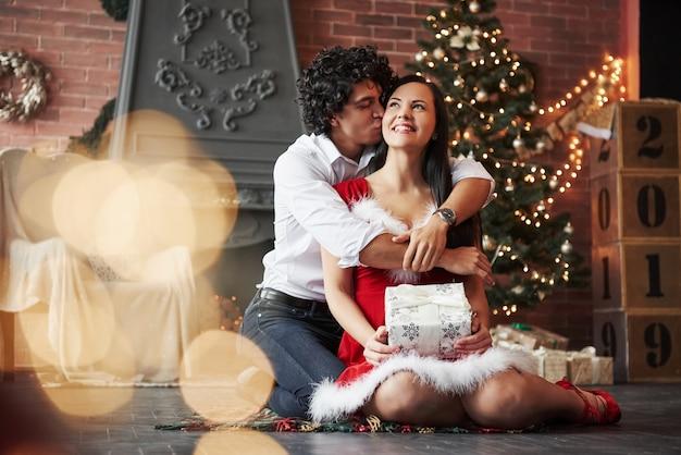 男は彼の女性にキスをします。クリスマスツリーと暖炉の後ろに飾られた部屋で新年を祝う美しいカップル