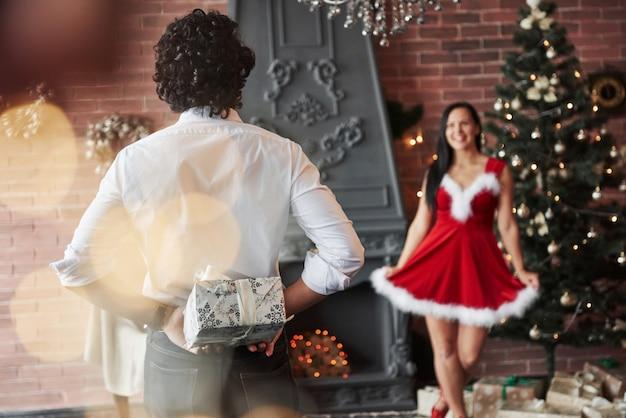 愛とプレゼントを共有する時間。男は立って、ギフトボックスの後ろに保持しています。赤いドレスを着た女性は彼氏からのクリスマスプレゼントを受け取るようになりました