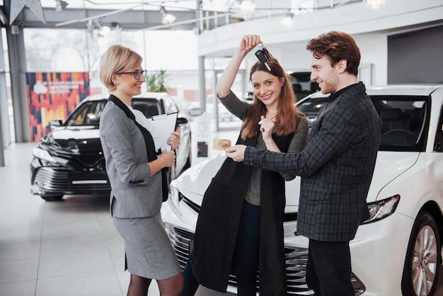 Наша первая машина. красивая счастливая женщина усмехаясь показывающ ключи нового автомобиля