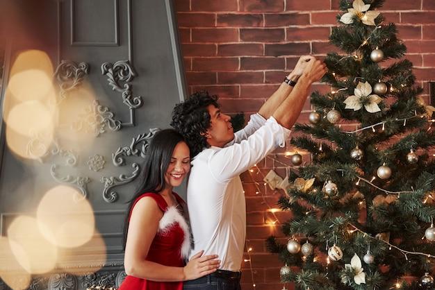 女の子が後ろに立っています。茶色の壁と暖炉のある部屋でクリスマスツリーをドレスアップするロマンチックなカップル
