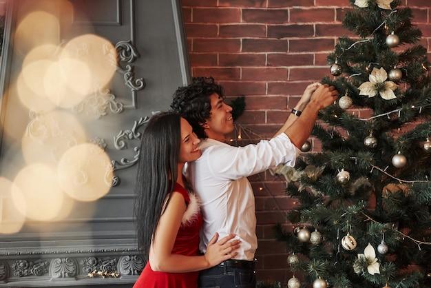 側面図。茶色の壁と暖炉のある部屋でクリスマスツリーをドレスアップするロマンチックなカップル