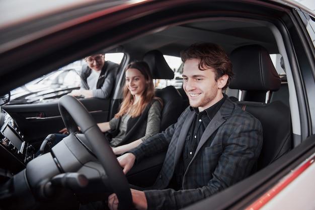 Принятие решения. красивая влюбленная пара сидит в новой машине вместе