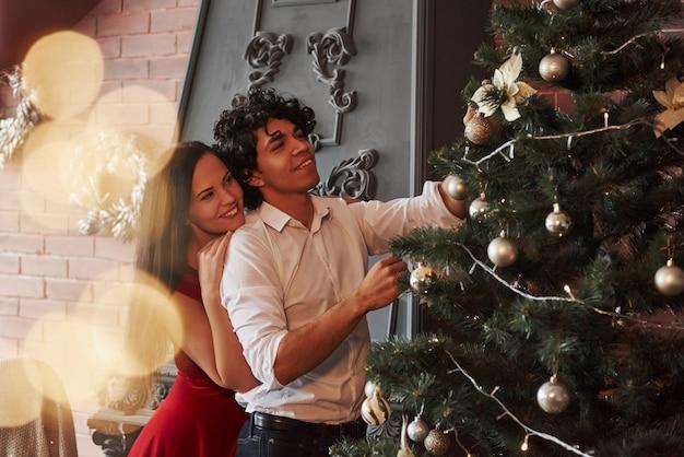 クラシックな装飾。茶色の壁と暖炉のある部屋でクリスマスツリーをドレスアップするロマンチックなカップル