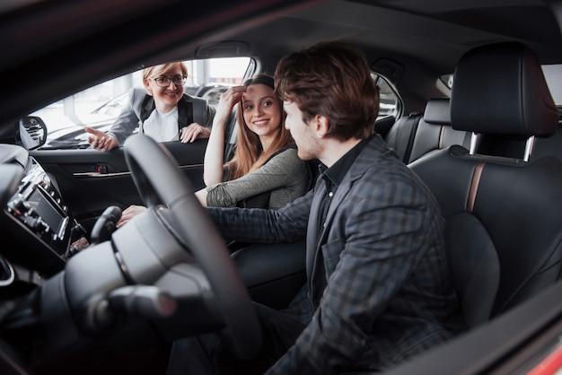 幸せな美しいカップルはディーラーで新しい車を選んでいます
