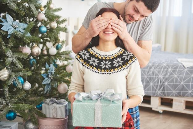 若いカップルがクリスマスを祝います。男が突然妻にプレゼントを贈った。家族の幸せと幸福の概念