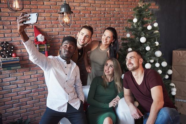 Группа старых веселых друзей общаются друг с другом и делают селфи фото. новый год наступает встречайте новый год в уютной домашней обстановке