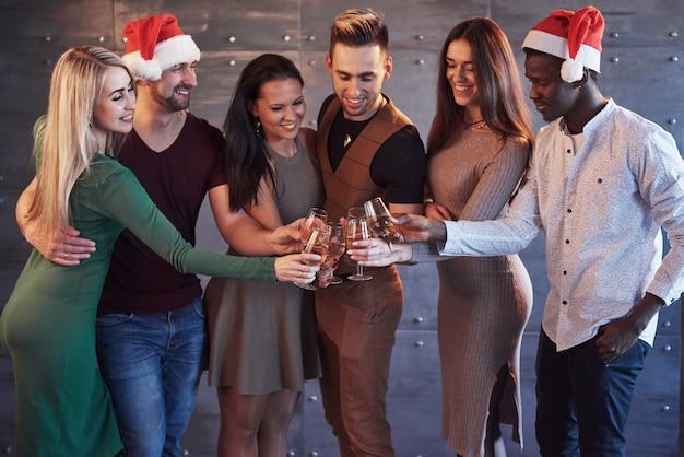 新年が来ています!感情的なライフスタイルの人々の概念をポーズ、パーティーのサンタ帽子で陽気な若い多民族の人々のグループ