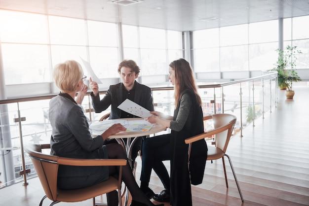 チームの仕事は成功します。オフィスで新しいスタートアッププロジェクトを扱う若いビジネスマネージャーの写真。