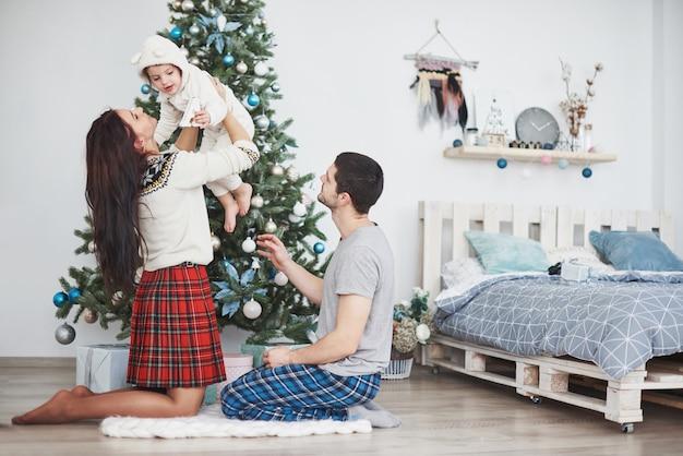 モミの木の近くで一緒に贈り物を開く朝のクリスマスに幸せな家族。