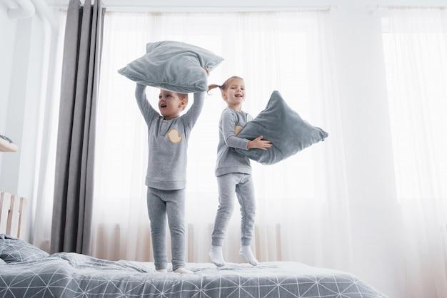 ベッドで遊んで柔らかく暖かいパジャマの子供たち