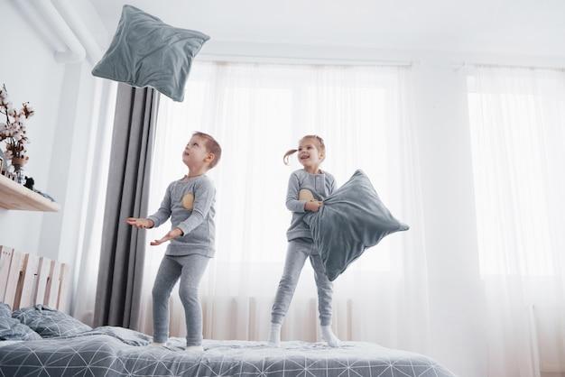 親のベッドで遊ぶ子供たち。子供たちは日当たりの良い白い寝室で目を覚ます。男の子と女の子は一致するパジャマで遊ぶ。子供と赤ちゃん用のパジャマと寝具。幼児の子供のための保育園のインテリア。家族の朝