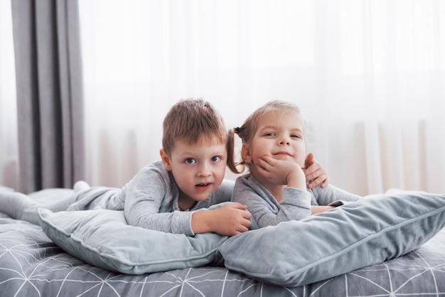 白い寝室で遊んでいる幸せな子供たち。男の子と女の子、弟と妹はパジャマを着てベッドで遊ぶ。子供のための保育園のインテリア。ベビーと幼児用のナイトウェアと寝具。自宅で家族