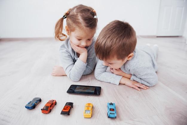 自宅でデジタルガジェットを使用している子供たち。パジャマ姿の兄と妹がテクノロジータブレットで漫画を見てゲームをする