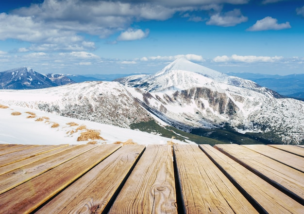 神秘的な冬の風景の雄大な山々とみすぼらしいテーブル。魔法の雪に覆われた木
