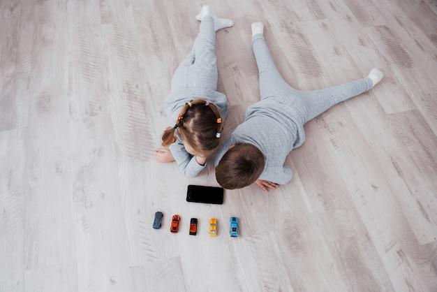上面図。自宅でデジタルガジェットを使用している子供たち。パジャマ姿の兄と妹がテクノロジータブレットで漫画を見てゲームをする