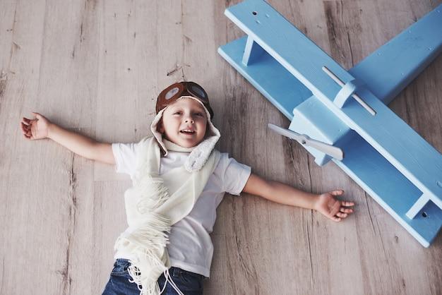 子供はパイロットのふりをします。家で楽しんでいる子供。ビンテージパイロットと旅行。トップビューの肖像画