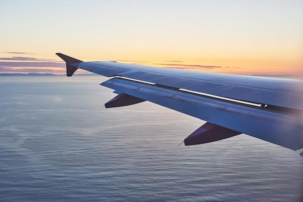 飛行機の翼で日の出をオーニングします。観光事業者に適用されます。テキストメッセージまたはフレームウェブサイトを追加するための画像。旅行