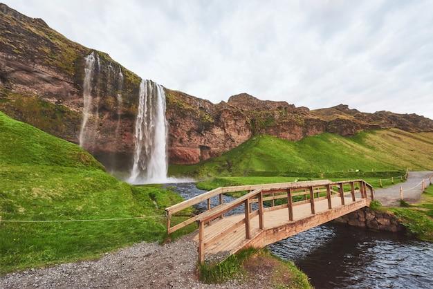 日没時のセリャラントフォスの滝。川に架かる橋。素晴らしい自然。アイスランド。