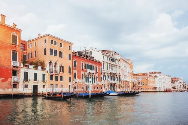 Большой канал венеции с гондолами и мостом риальто, италия в яркий летний день