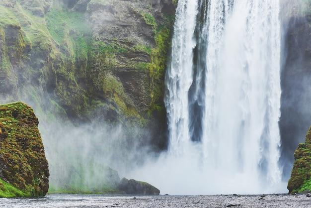 Большой водопад скогафосс на юге исландии недалеко от города скогар. драматическая и живописная сцена