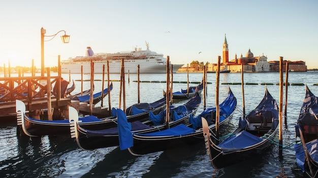 Гондолы в венеции - закат с церковью сан-джорджо маджоре. венеция, италия
