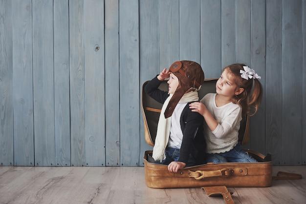 パイロット帽子と小さな女の子が古いスーツケースで遊んで喜んでいる子供。子供の頃。ファンタジー、想像力。旅行