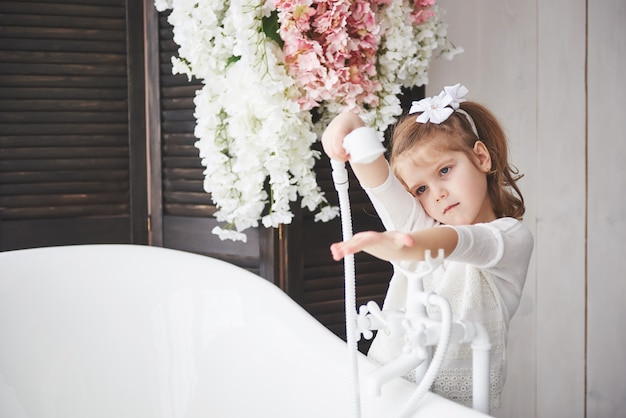 Смешная маленькая девочка с вьющимися волосами. будьте готовы принять ванну. просторная светлая ванная комната. здоровое и чистое тело. забота о себе с детства