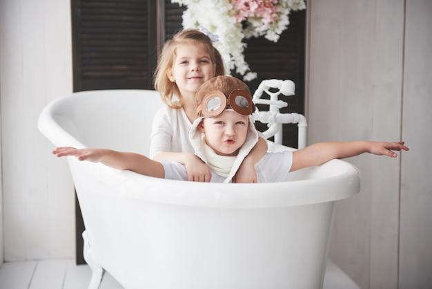 女の子とパイロットや船員のトイレで遊んでいるパイロット帽子の少年の肖像画。旅行、子供時代、夢の実現