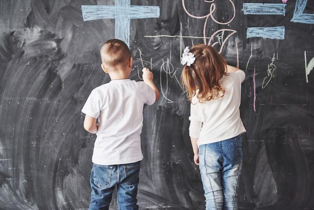 かわいい女の子と男の子が壁にクレヨン色で描きます。子供の仕事。黒板に書くかわいい生徒