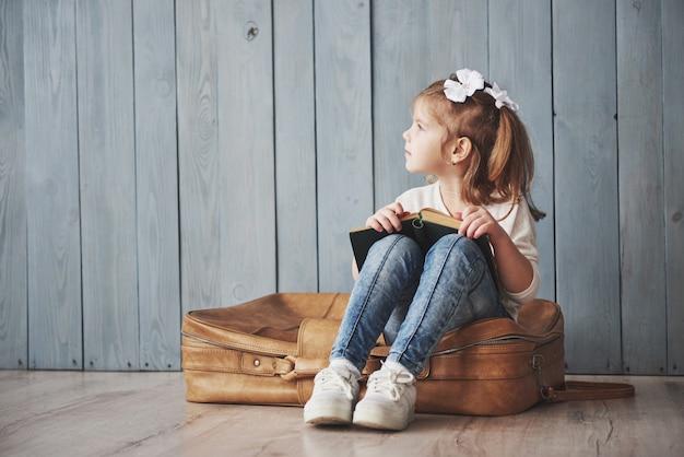 Готов к большим путешествиям. счастливый маленькая девочка, читая интересную книгу, перевозящих большой портфель и улыбается. путешествие, свобода и воображение