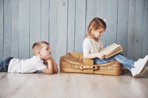 Готов к большим путешествиям. счастливое чтение книги маленькой девочки и мальчика интересное нося большой портфель и усмехаться. путешествие, свобода и воображение