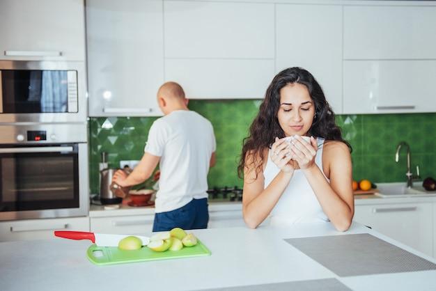 キッチンでコーヒーを飲んで幸せな若いカップル
