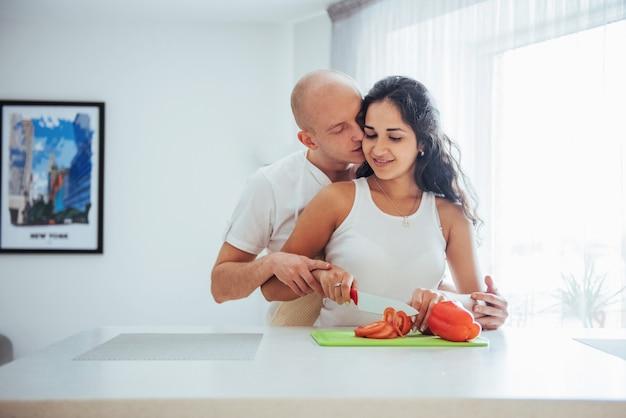美しい若いカップルは、台所で野菜を一緒に挽きます。