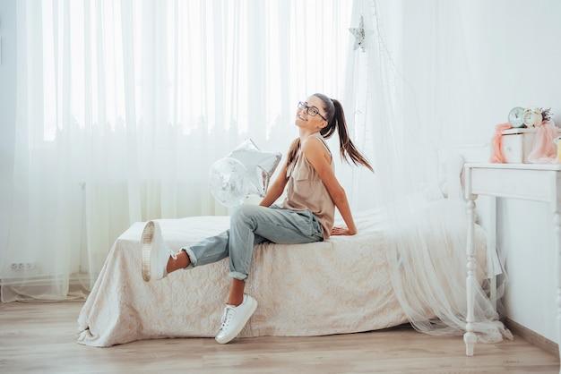 クローズアップかわいいブルネットの少女、広く笑って、透明と銀の風船で遊ぶ。