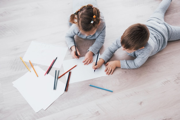 子供たちはパジャマ姿で床に横になり、鉛筆で描きます。鉛筆で描くかわいい子