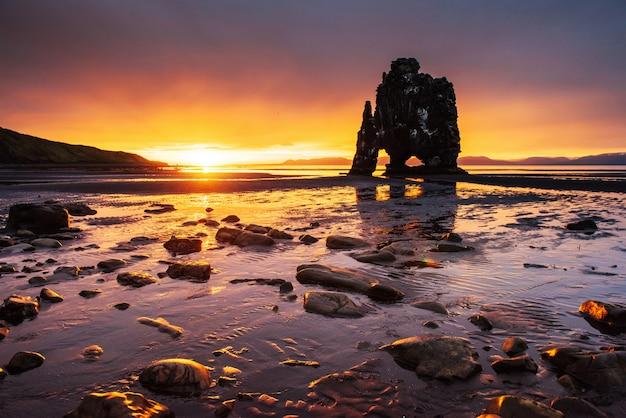 Это эффектная скала в море на северном побережье исландии. легенды говорят, что это окаменевший тролль. на этом хвицеркур отражается в морской воде после полуночного заката
