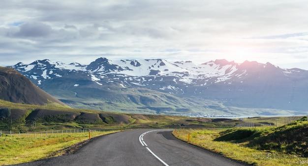 Путешествие в исландию. дорога в яркий солнечный горный пейзаж. вулкан ватна, покрытый снегом и льдом на тнэ