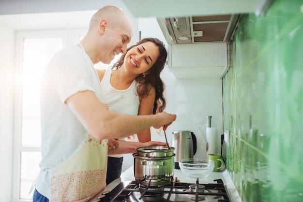 Счастливая молодая пара готовится на плите