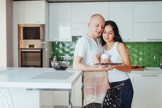 美しい若いカップルは、自宅のキッチンで料理をしながら笑顔をグラフ化。