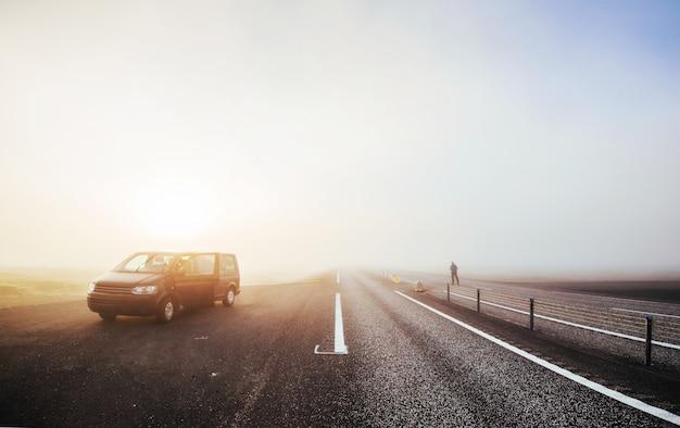 Автобус на перевале. путешествие в исландию. красивый закат над океаном и фьордом в исландии. исландский пейзаж с горами и облаками