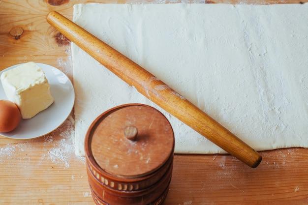 Кусок свежеприготовленного теста раскатывают на муковой рабочей поверхности деревянной скалкой