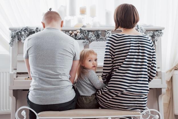 白いピアノを弾く母父と娘を後ろから見る