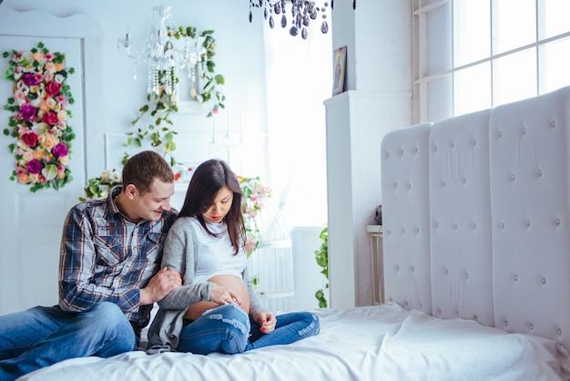 Беременная женщина и ее муж держат пинетки