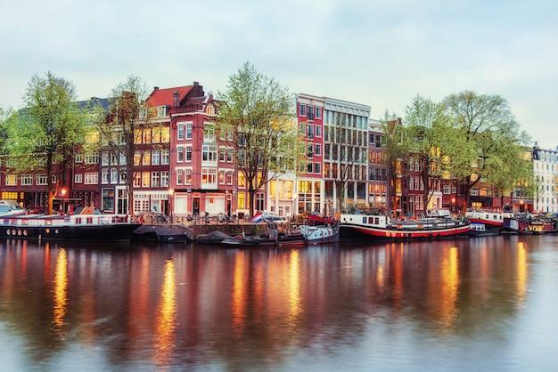 活気のある反射と夕暮れ時にアムステルダムの運河の家