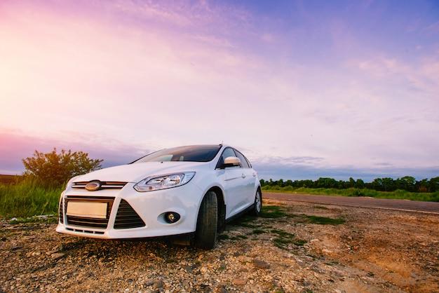 Спортивный автомобиль белого цвета на природе.
