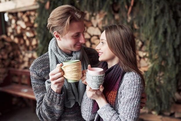 冬の屋外のロマンチックなキャビンで朝食を持っている若いカップル。冬の休日と休暇。幸せな男と女のクリスマスカップルは、ホットワインを飲みます。愛のカップル