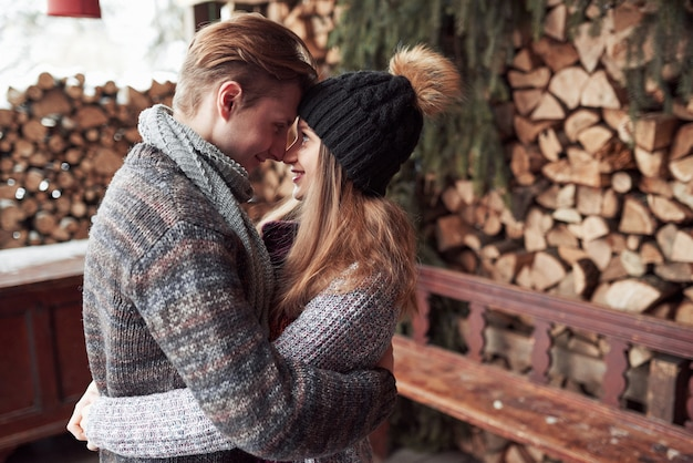 冬、休暇、カップル、クリスマス、人々-帽子とスカーフの木製のカントリーハウスと雪を抱いて笑顔の男性と女性