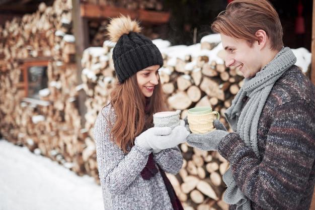 幸せな男と冬に屋外のカップを持つきれいな女性の写真。冬の休日と休暇。幸せな男と女のクリスマスカップルは、ホットワインを飲みます。愛のカップル