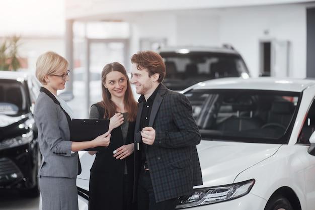 Готов к поездке! великолепные влюбленные, позирующие вместе возле своей новой машины в салоне автосалона, счастливо улыбаясь, показывая ключи от машины в аренду, покупая благополучие