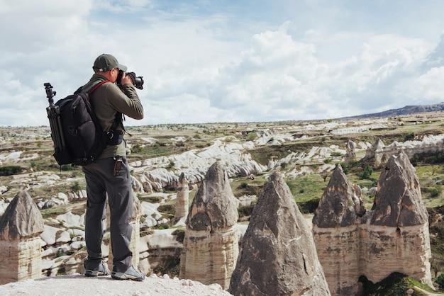 男は、山の愛の谷の写真を撮ります。キャップパッド